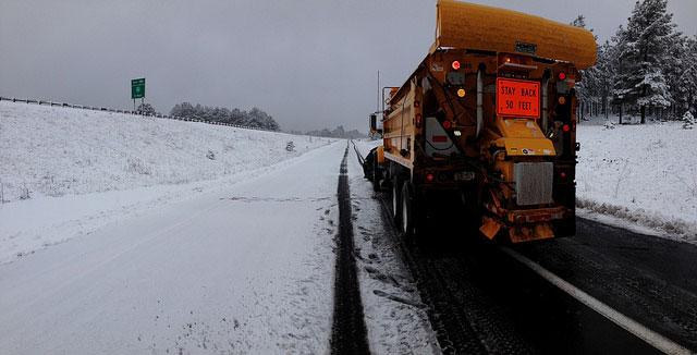 Rear View of a Snow Plow Clearing a Highway