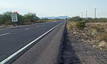 Millings from the old, worn roadway are used to build up the road's shoulder. along US 60