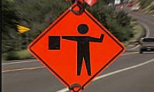 Safety orange diamond sign with figure of flagger beside roadway