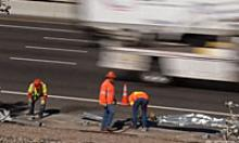 ADOT workers removing debris from the shoulder of a highway as vehicle speed by.