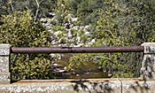 Stone and pipe railing overlooking a creek