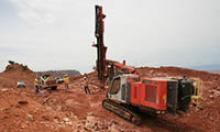 Construction equipment works in red dirt