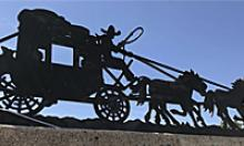 Silhouette of a stage coach, driver and horses in full gallop.