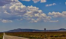 Cumulus clouds hang in a blue sky over lonely two lane road stretching towards mountains in the distance.