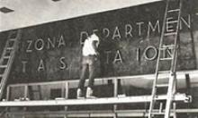 Workman on scaffold affixes letters spelling out Arizona Department of Transportation on the side of the Administration Building.