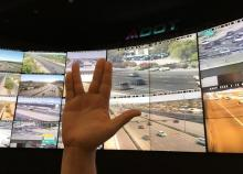 Vulcan hand greeting in front of Traffic Operations Centers wall of traffic monitors.