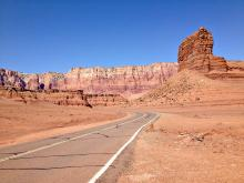 Desolate roadway towards rock cliffs and formations.