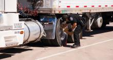 ECD Officer check a tractor trailers tires at an inspection station.