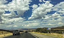 Puffy white clouds stream across the sky over roadway.