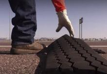 Worker picks up shredded tire from roadway.