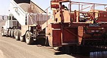 Large paving vehicle apply tack coat to roadway.