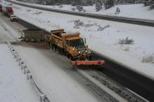 Tow snow plow clears snow along I-40.