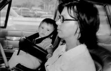 Archive photo of woman driving with child in car seat in front of the car.