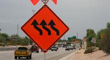 Orange 3 Lane Reverse Curve warning sign with roadway in the background.