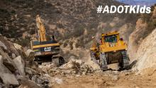 Zoom meeting background showing heavy equipment moving rocks