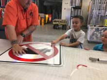 Adam Wilt (left) of ADOT's Sign Factory makes a sign for Hunter Vincente