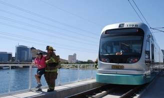Firefighter participating in mock emergency - shown here rescuing person near Valley Metro Rail Car